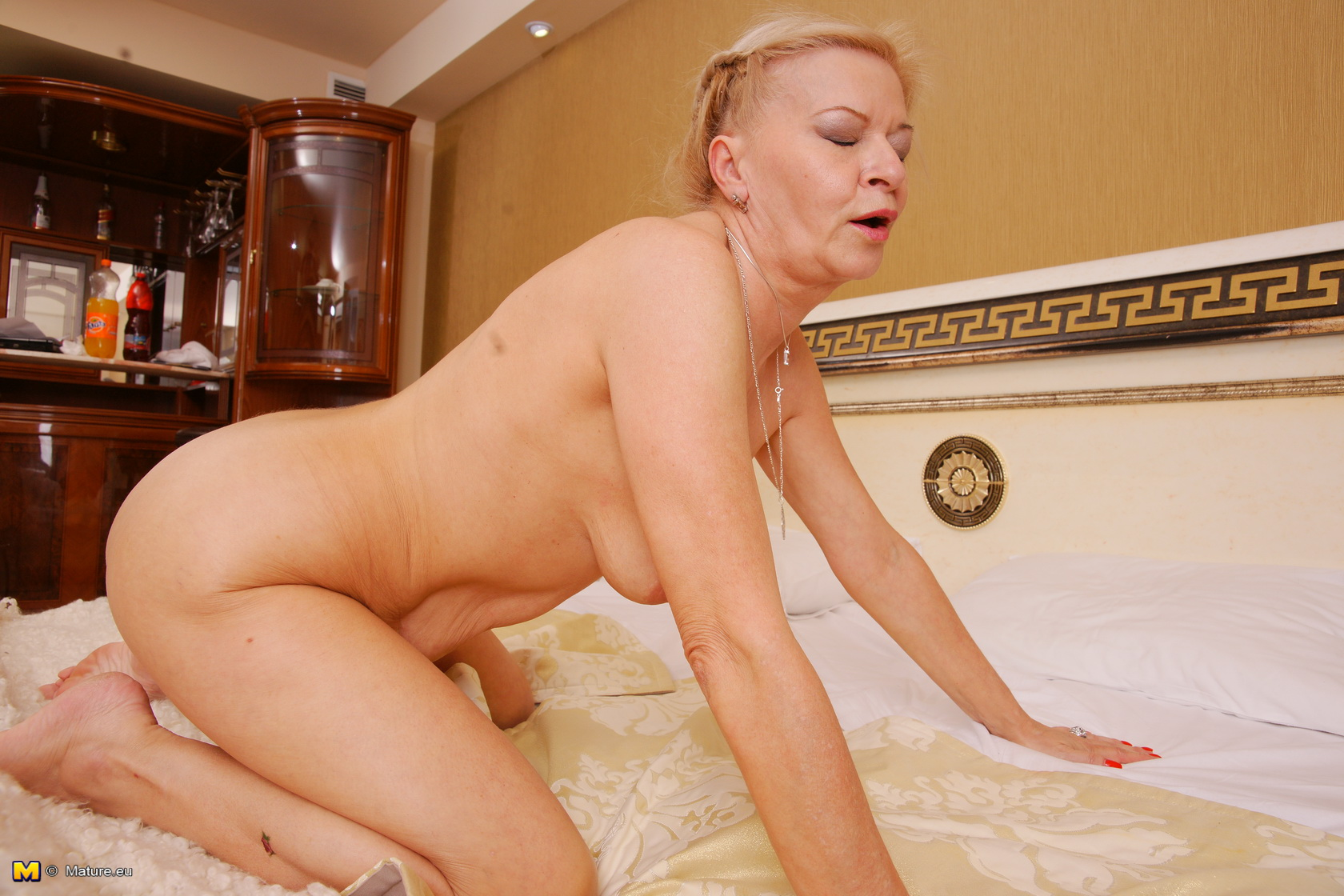 Blonde mature slut masturbating on her bed
